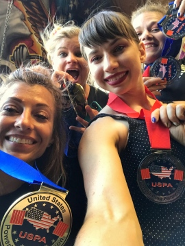Four women in a selfie show off their powerlifting medals